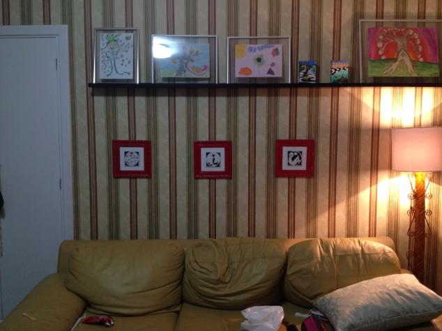 O de listra atrás do sofá. Os quadrinhos de azulejo estão pregados com aqueles ganchos sem furos. São da Cris Conde. os outros são das minhas artistas, â exceção dos do Rio, que são de uma artista muito querida, Megg Rai.