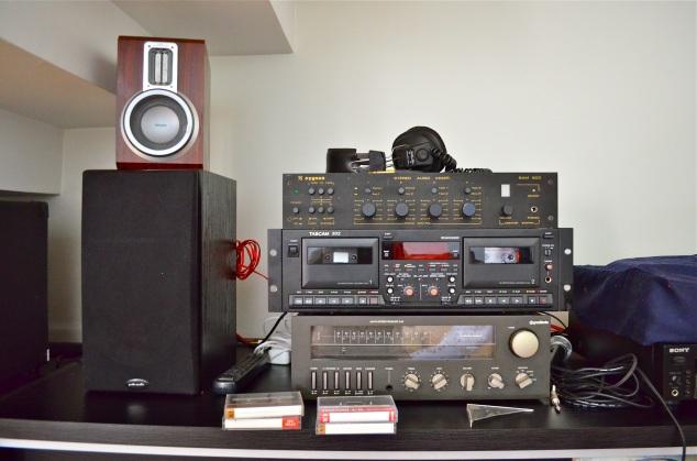 Em cima do móvel ficam os equipamentos de música e outro dia Marcão me falou que já tinha tido que queria. Tem um mixer, um receiver, uma vitrola Stanton (coberta com capa), um toca-fitas que grava, um carrosel de CDs que grava, também.  Distingo pouco qual é qual.