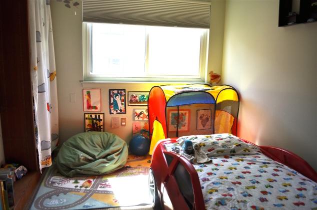 Geral do quarto: parede da estante à esquerda, janela, parede da cama e a quarta parede tem o armário.