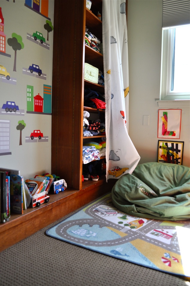 Cantinho da leitura, com tapete, pufe e livrinhos… A parte que a cortina de carros cobre ficou sendo o armário do Léo! <3