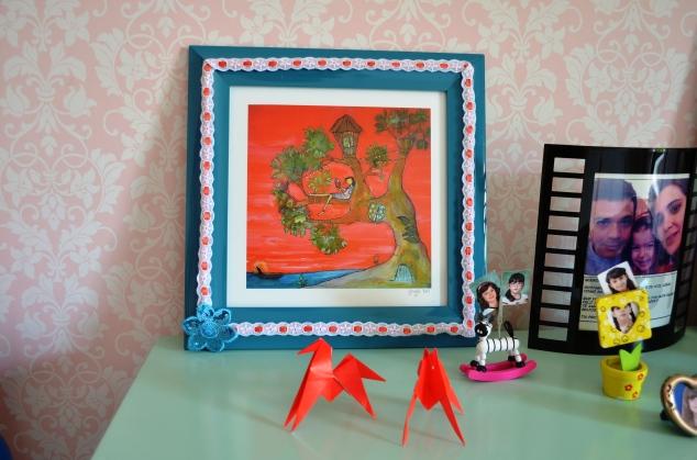 Alguém lembra deste quadrinho da Johanna Wright do meu IG ( @deolhonacasa) ? Preguei com os velcros Command, caiu no chão, lascou toda a moldura :(  Cola quente, um passa-fitas e uma flor de lantejoulas que sobrou da outra capa, ei-lo de volta à vida!!!