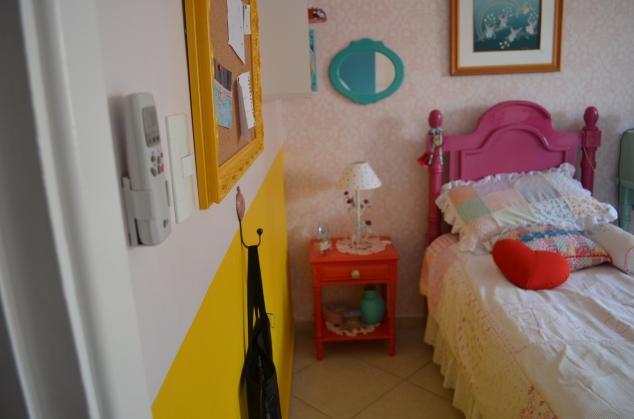 Em cima do criadinho colocamos o espelho azul turquesa da @avoqueria, amiga querida que ganhei neste processo todo. E o quadro com anjos da Lígia Lages sobre a cama. E a meia parede amarela com os carregadores dela...