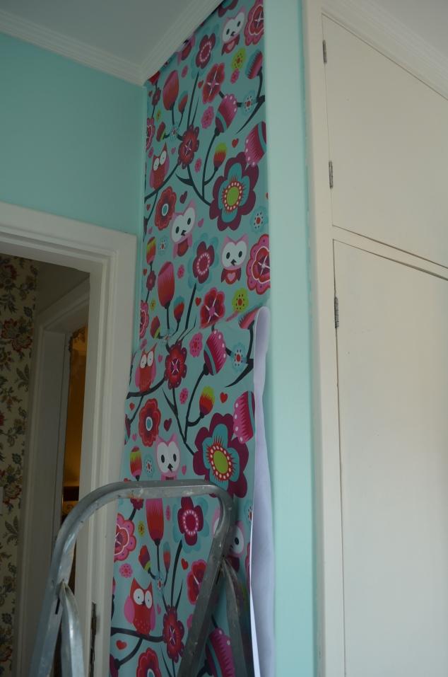 Aplicando adesivo vinílico na parede... Apliquei outra estampa nas gavetas de uma cômoda também.
