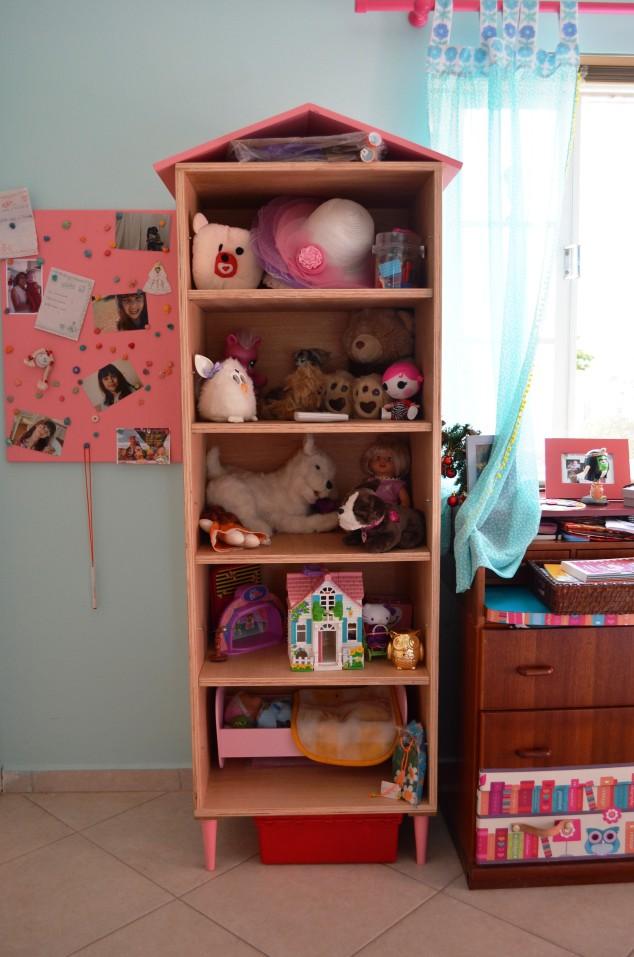 casinha-estante com pés-palito pintados de rosa.