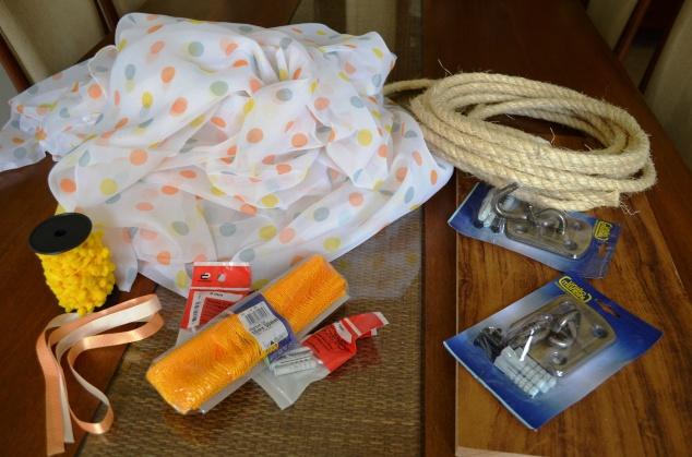 voil de cortina ( comprei 3m com 2,80m de largura); corda de sisal ( 12m); fita de cetim larguinha ( 1m); 2 suportes de rede ( já vem com buchas e parafusos); 4 ganchos 8 ( suporta 100kg); um pedaço de MDF ( retalho do Leroy); máquina de costura e furadeira. Pompons greló e washitape são alternativos.