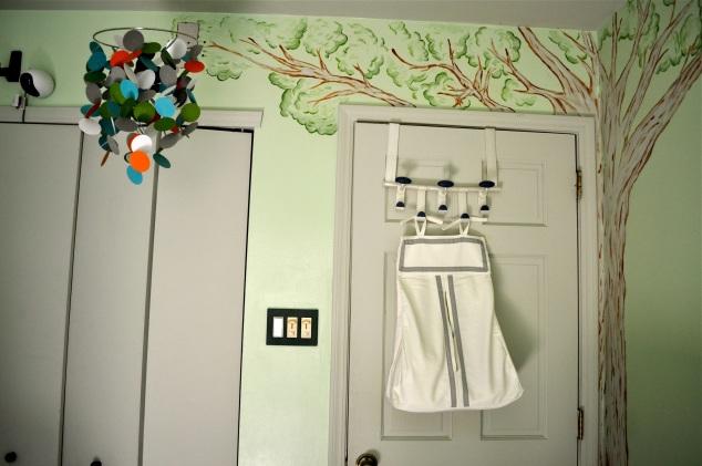 Como o quarto é pequeno, as fraldas ficam acomodadas atrás da porta.