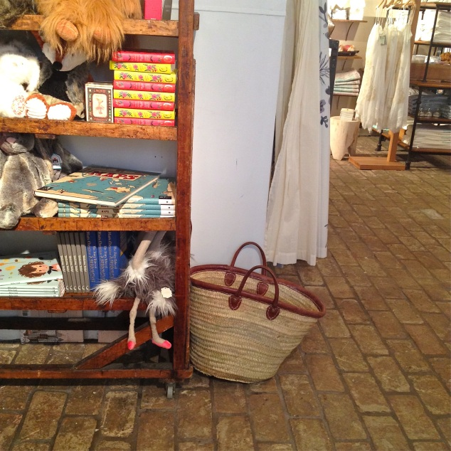 Esta é a sacola de compras, de palha, aí no cantinho… Na estante tem livros e vasos em forma de livros… e pelúcias...
