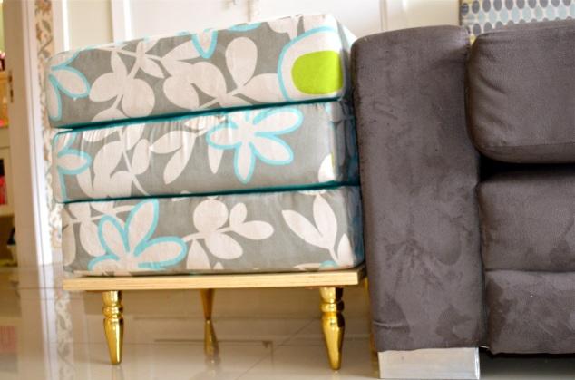 O antigo assento do sofá se assenta numa base de compensado com pés-palito dourados...